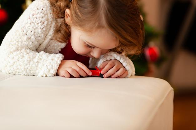 Małe dziecko bawi się małym samochodzikiem.