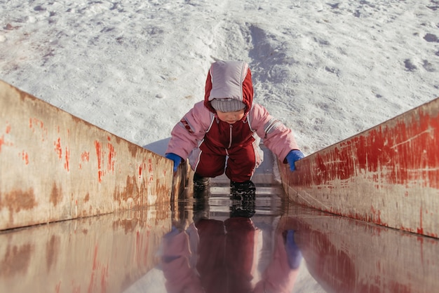 Małe dziecko bawi się na placu zabaw w zimie
