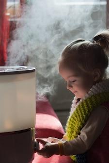 Małe dziecko bawi się nawilżaczem