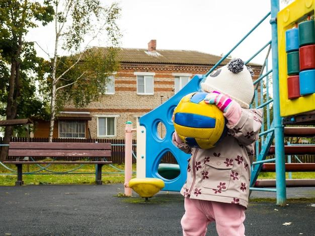 Małe dziecko bawiące się piłką na placu zabaw w jesienny dzień