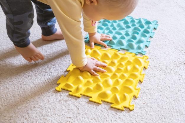 Małe dziecko bawiące się prążkowanym dywanem.