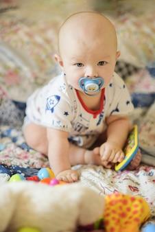 Małe dziecko bawiące się zabawkami na łóżku