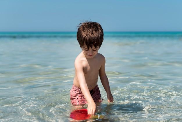 Małe dziecko bawić się z wiadrem w wodzie
