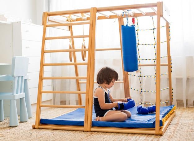 Małe dziecko bierze udział w boksie na drewnianym kompleksie sportów domowych. dziewczyna w rękawice bokserskie uderza gruszkę.