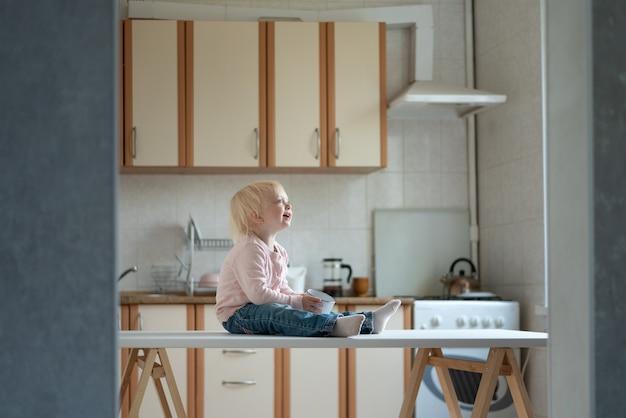 Małe dziecko blondynka siedzi na stole w kuchni. współczesne dzieci. ranek.