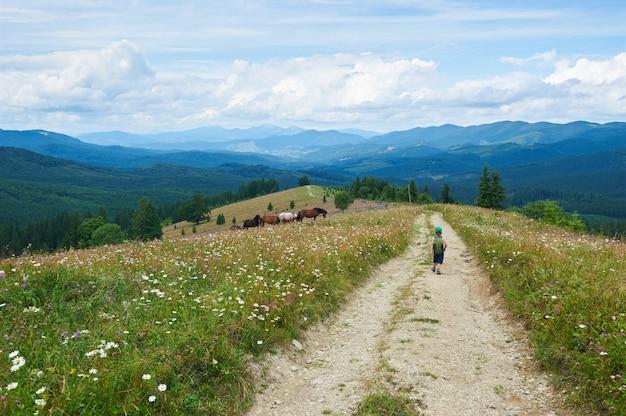 Małe dziecko chłopiec chodzi samotnie w górach. widok z tyłu