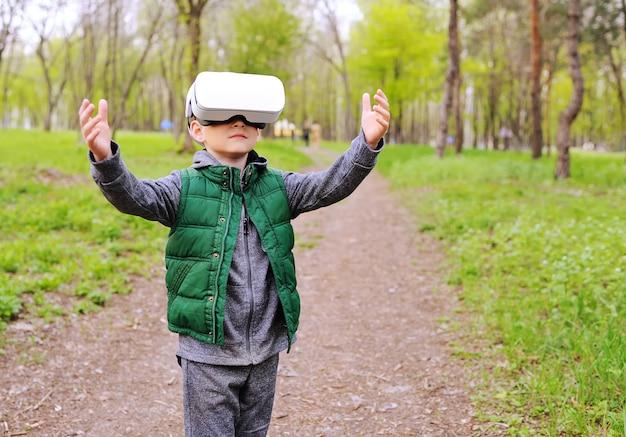 Małe dziecko chłopiec w szkło rzeczywistości wirtualnej na powierzchni zieleni i lasu.