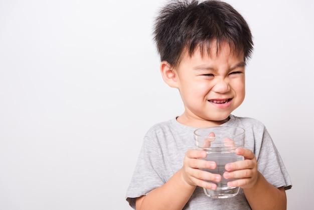 Małe dziecko chłopiec woda pitna od szkła