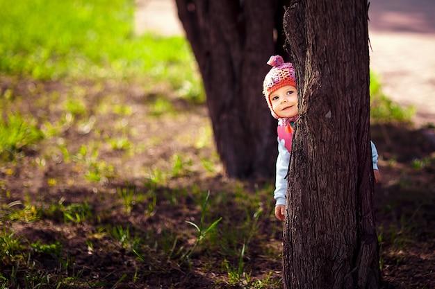 Małe dziecko chuje się za drzewem