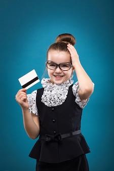 Małe dziecko ciemne włosy z kartą kredytową ubrane jak nauczyciel w czarną sukienkę