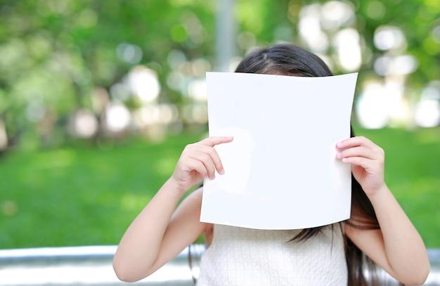 Małe dziecko dziewczyna chuje twarz za pustym białym papierem w zielonym ogródzie.
