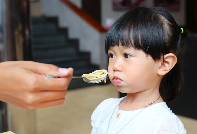 Małe dziecko dziewczyna je nudnego jedzenie.