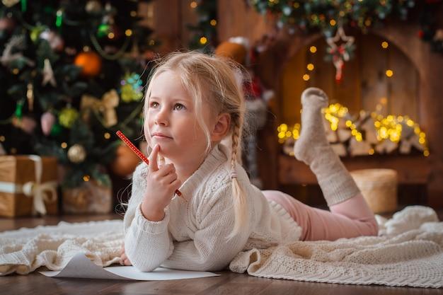 Małe dziecko dziewczyna pisze liście święty mikołaj
