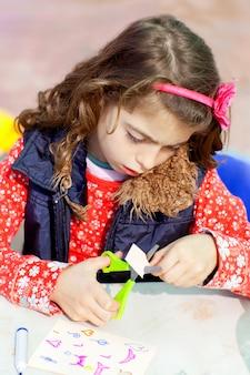 Małe dziecko dziewczyna pracuje w szkole robi warsztaty