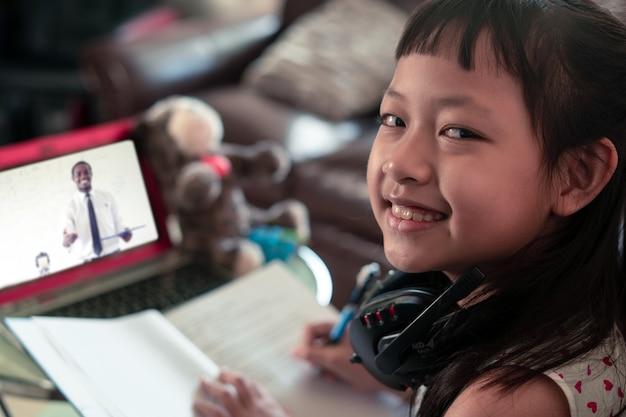 Małe dziecko dziewczyna uczy się na laptopie w domu, socjalny odległość podczas kwarantanny, online edukaci pojęcie