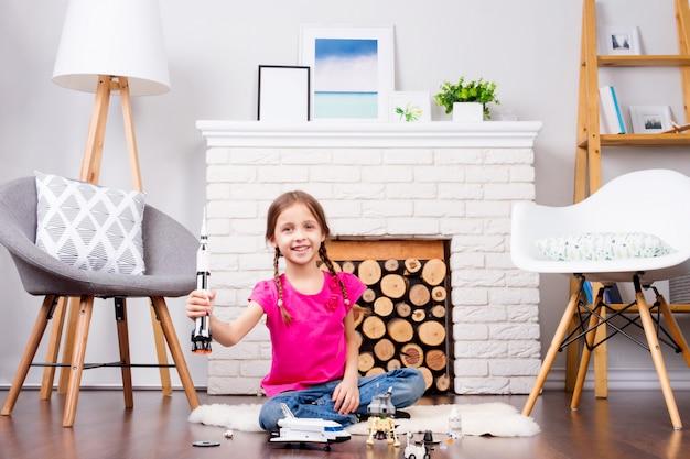 Małe dziecko dziewczynka bawi się konstruktorem zabawek kosmosu: rakietą, promem, łazikiem, satelitą i lalką astronautów w wygodnym wnętrzu w domu na drewnianej podłodze