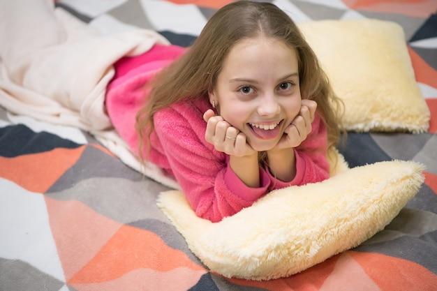 Małe dziecko dziewczynka gotowy do snu. czas na odpoczynek. dzień dobry. międzynarodowy dzień dziecka. mała szczęśliwa dziewczyna w sypialni. szczęście z dzieciństwa. piżama party. dobranoc. słodkie sny.