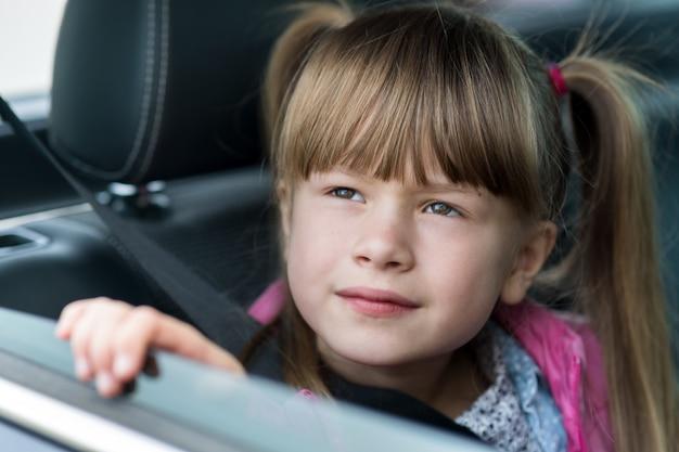 Małe dziecko dziewczynka siedzi w samochodzie na tylnym siedzeniu zapinanym pasem bezpieczeństwa.
