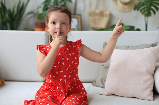 Małe dziecko dziewczynka trzymając palec na ustach i prosząc o zachowanie ciszy.