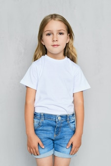 Małe dziecko dziewczynka w biały t-shirt, dżinsy i różowe trampki pozuje blisko ściany