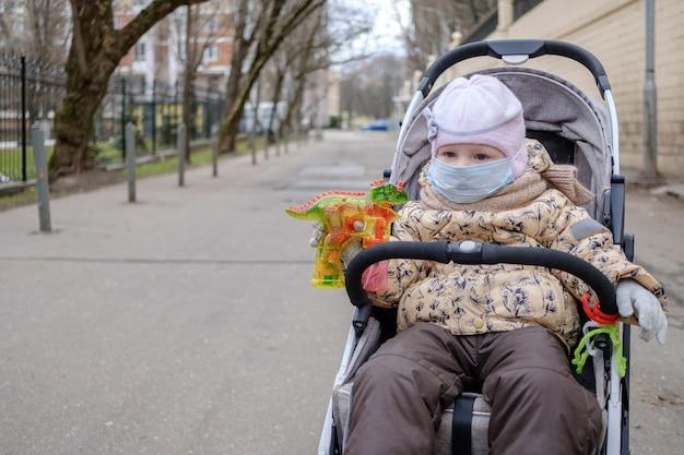 Małe dziecko dziewczynka w masce ochronnej na twarzy siedzi w wózku