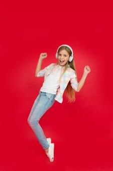 Małe dziecko dziewczynka w słuchawkach. szczęście z dzieciństwa. odtwarzacz mp3. dzień dziecka. technologia audio. małe dziecko słuchać ebooka, edukacja. posłuchać muzyki. uroda i moda. muzyka to świetna zabawa.