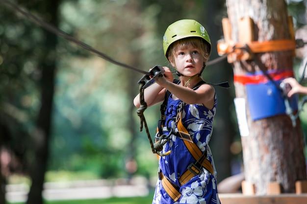 Małe dziecko dziewczynka w uprzęży bezpieczeństwa i hełmie przymocowanym do kabla porusza się ostrożnie wzdłuż liny w parku rekreacyjnym.