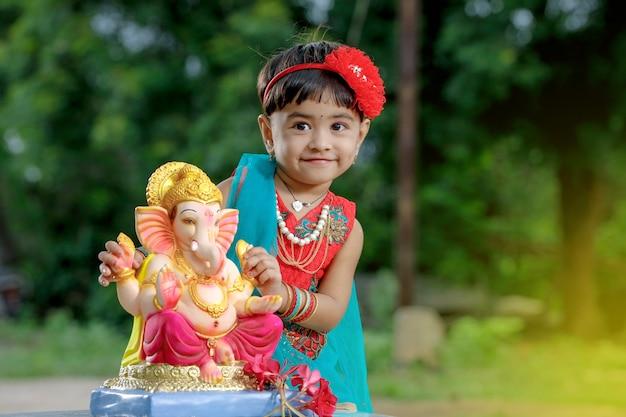 Małe dziecko indian dziewczyna z pana ganesha i modląc się