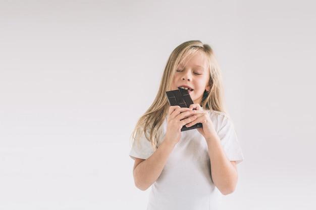 Małe dziecko je czekoladowego bar. blondy dziewczyna odizolowywająca na bielu.