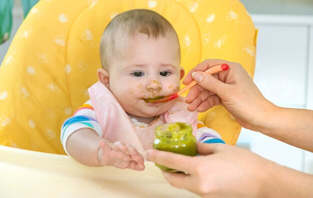 Małe dziecko je przecier warzywny z brokułów. selektywna ostrość. ludzie.