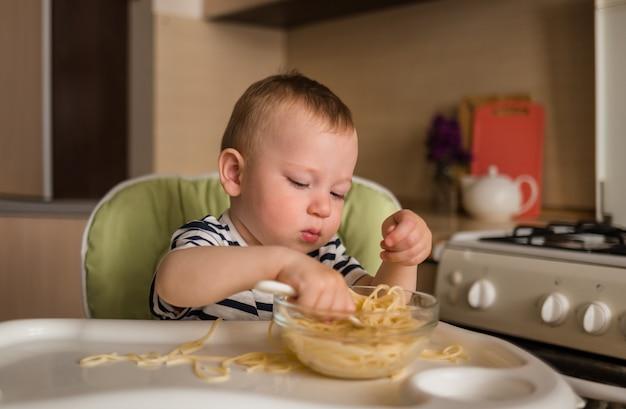 Małe dziecko je spaghetti przy wysokim stole w kuchni. nauka samodzielnego jedzenia.