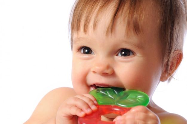 Małe dziecko jednego roku trzyma pod ręką kolorową zabawkę ząbkowanie.