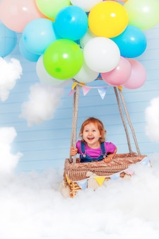 Małe dziecko lata na pakiecie kolorowych balonów wypełnionych helem, stojących w drewnianym koszu pilota. położony na niebie wśród chmur. dekoracja nieba