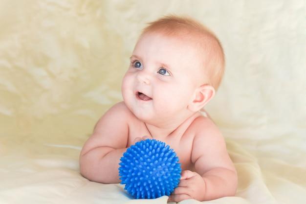 Małe dziecko leżące na brzuchu i trzymające piłkę do masażu