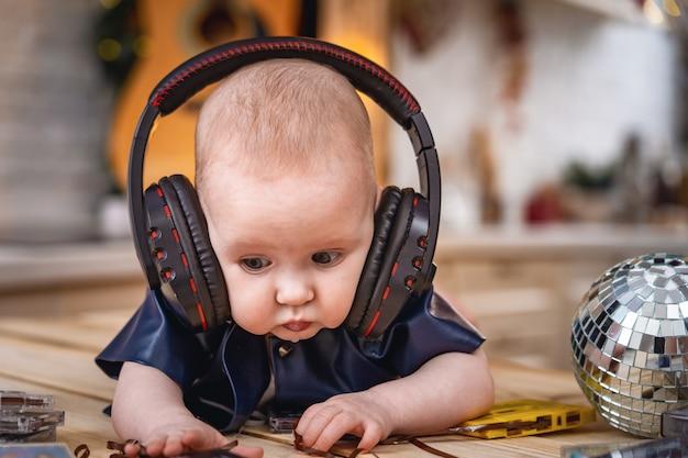 Małe dziecko leży na brzuchu ze słuchawkami i słucha muzyki