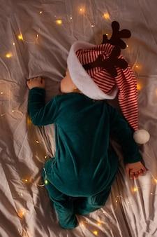 Małe dziecko leży na łóżeczku w świątecznym kostiumie i czapeczce z rogami jelenia. boże narodzenie i nowy rok.
