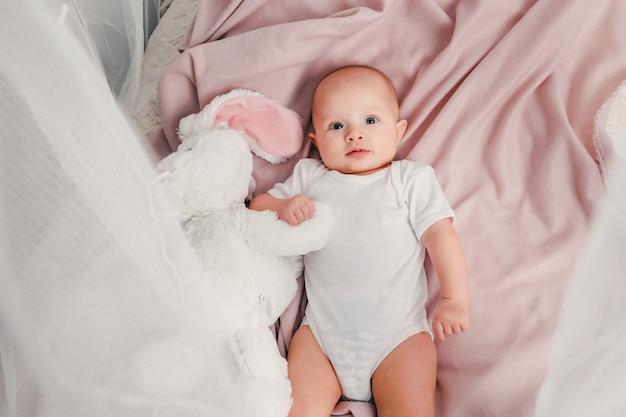 Małe dziecko leży na łóżku z zabawkowym królikiem i uśmiecha się