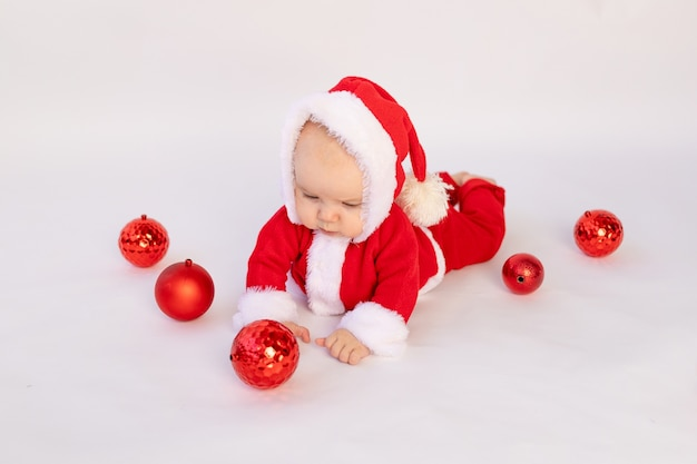 Małe dziecko leży w stroju świętego mikołaja z czerwonymi bombkami, koncepcja bożego narodzenia