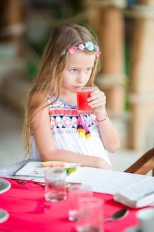 Małe dziecko ma śniadanie przy plenerową kawiarnią. urocza dziewczyna pije świeżego arbuza sok cieszy się śniadanie.
