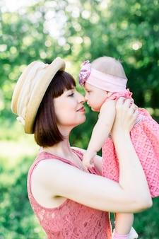 Małe dziecko, mała dziewczynka siedząca na kolanach matki, patrząca sobie w oczy, przytula ją, ciepły i słoneczny dzień w parku na ulicy na trawie