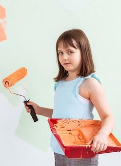Małe dziecko malarz robi renowację ściany