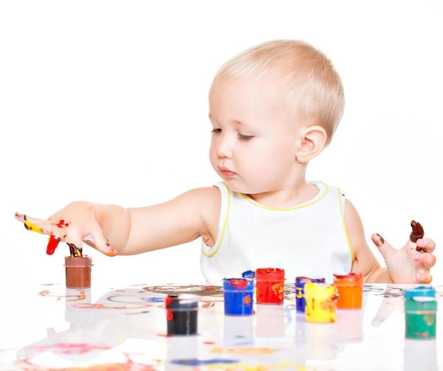 Małe dziecko maluje rękami - na białej ścianie.