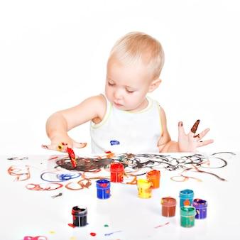 Małe dziecko maluje rękami na białym tle.