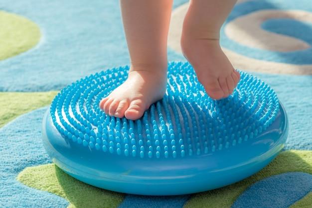 Małe dziecko masuje stopy stojąc na dywanie