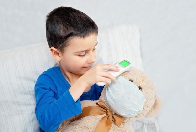 Małe dziecko mierzy temperaturę niedźwiedzia zabawkowego w masce przeciw zanieczyszczeniom za pomocą nowoczesnego termometru cyfrowego na podczerwień.