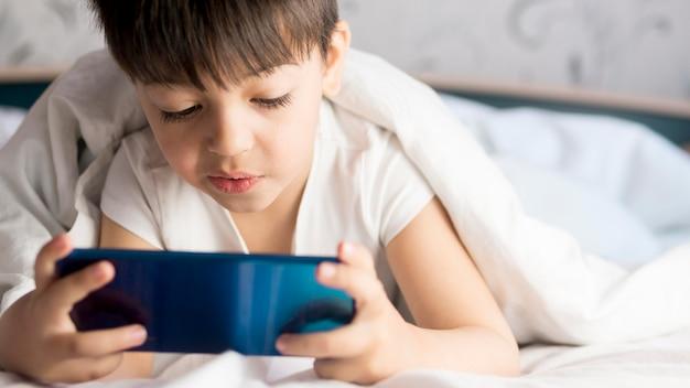 Małe dziecko na telefonie z łóżkiem