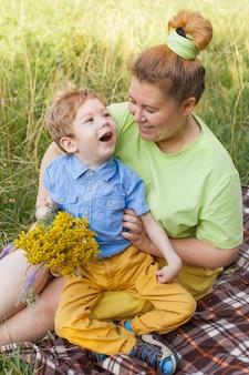 Małe dziecko na wózku inwalidzkim bawi się z mamą na świeżym powietrzu. życie w wieku edukacyjnym dzieci niepełnosprawnych, koncepcja szczęśliwego dziecka niepełnosprawnego.