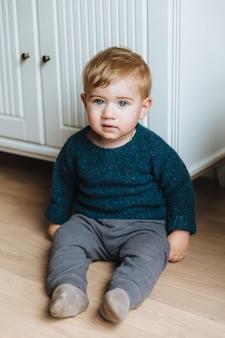 Małe dziecko o atrakcyjnych niebieskich oczach, pulchnych policzkach i blond włosach siedzi na podłodze