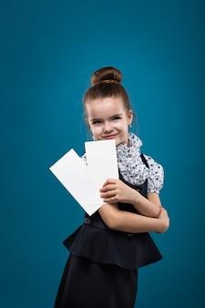 Małe dziecko o ciemnych włosach z papierami ubranymi jak nauczyciel w czarną sukienkę