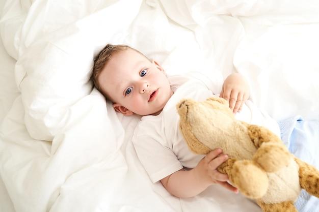 Małe dziecko o niebieskich oczach trzyma zabawkę leżącą na łóżku. widok z góry.